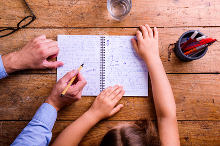 writing desk: Unrecognizable father and son studying together, writing into notebook. Studio shot on wooden background. Flat lay. Stock Photo