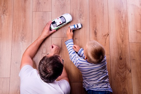 adult toys: Unrecognizable father with his son playing with cars. Studio shot on wooden background.