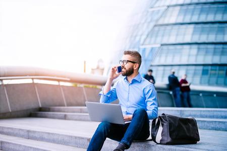 the working day: gestor de última moda hermoso que se sienta en las escaleras en día soleado, trabajando en equipo portátil, hablando por un teléfono inteligente, Londres, Ayuntamiento