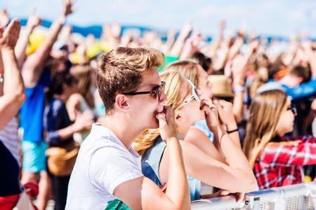 在夏天音乐节的青少年在享受自己的人群的阶段,吹口哨