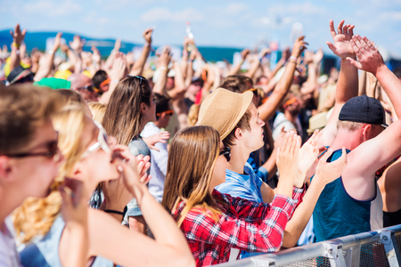 자신을 즐기고, 휘파람을 불고, 박수 치고, 노래하는 군중의 무대 아래 여름 음악 축제에서 청소년들