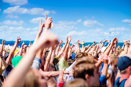 Teenagers at summer music festival under the stage in a crowd enjoying themselves, clapping and singing Stock Photo