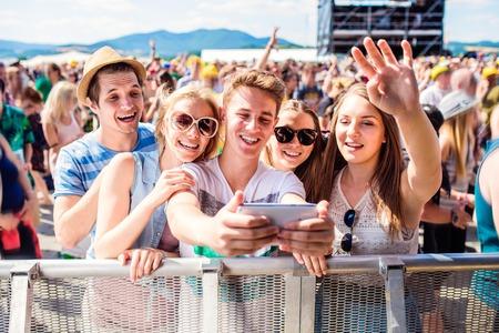 Tieners in de zomer muziekfestival in menigte nemen selfie met smartphone, genieten van zichzelf