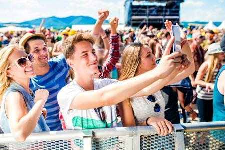 祭り: 自分自身を楽しんで、スマート フォンで selfie を取って群衆の中に夏の音楽祭でティーンエイ ジャー