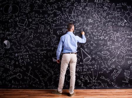 hombre escribiendo: profesor inconformista escribiendo en gran pizarra con símbolos y fórmulas matemáticas. Foto de estudio sobre fondo negro. Vista trasera