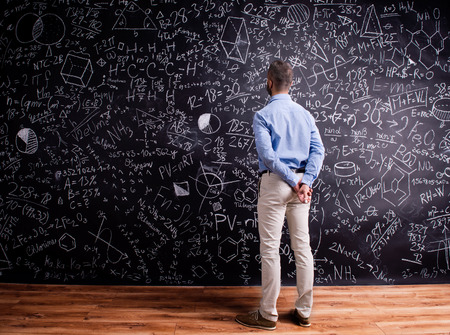 big behind: Hipster teacher standing against big blackboard with mathematical symbols and formulas, hands behind back. Studio shot on black background. Rear view.