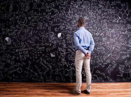 hands behind back: Hipster teacher standing against big blackboard with mathematical symbols and formulas, hands behind back. Studio shot on black background. Rear view.