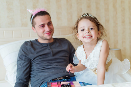 dress up: Cute little girl in princess dress putting on colorful make up on her father