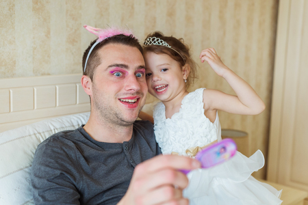 dad and daughter: Cute little girl in princess dress that put on colorful make up on her father