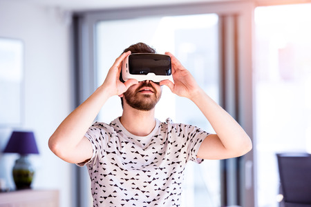 Young hipster man wearing virtual reality goggles, standing in living room