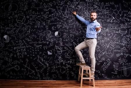 step ladder: Hipster teacher writing on big blackboard with mathematical symbols and formulas, standing on step ladder. Studio shot on black background.