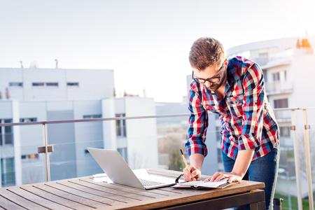 青年実業家のラップトップ コンピューターで作業して、バルコニーに立って、手帳への書き込み