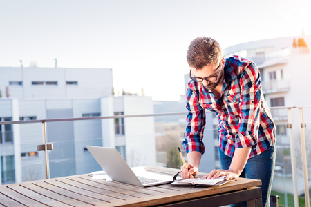 personal organizer: Young businessman working on a laptop computer, standing on the balcony, writing into personal organizer Stock Photo