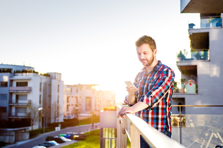 person reading: Hipster businessman in checked shirt with smart phone texting, standing on balcony