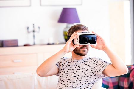 hombre inconformista joven que llevaba gafas de realidad virtual, sentado en la sala