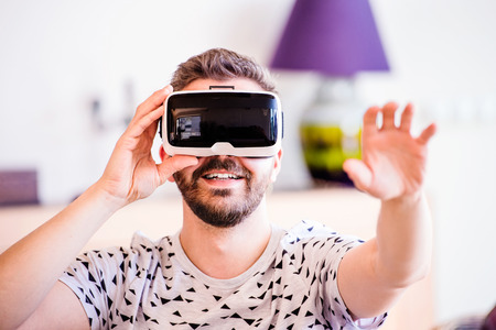 man sit: Young hipster man wearing virtual reality goggles, sitting in living room Stock Photo