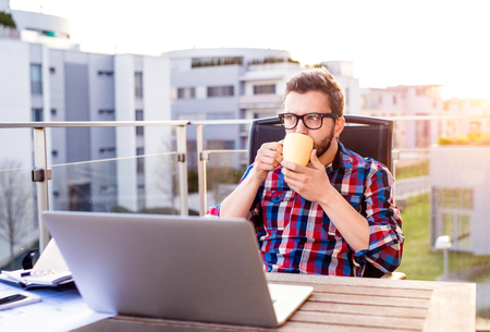 Hipster businessman with laptop in checked shirt sitting on a balcony, holding a cup of coffee, relaxing Foto de archivo