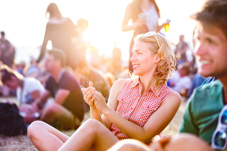 girl in shorts: Group of teenagers at summer music festival, sitting on the ground, teenage girl with blond curly hair, checked shirt