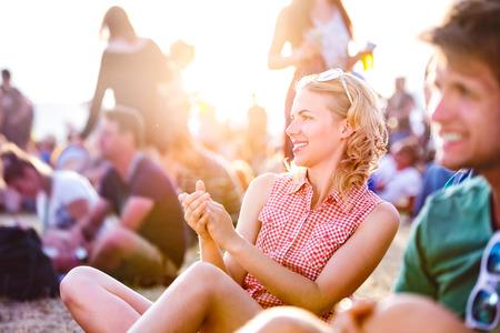 niño y niña: Grupo de adolescentes en el festival de música de verano, sentado en el suelo, adolescente con el pelo rizado rubio, camisa a cuadros