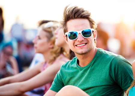 earing: Hipster teenage boy in green t-shirt and sunglasses with his friends at summer music festival, sitting on the ground Stock Photo