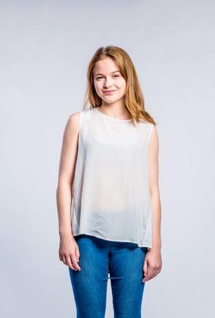 jeans apretados: Adolescente en pantalones vaqueros y camiseta blanca, mujer joven, tiro del estudio sobre fondo gris