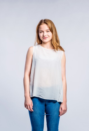 Teenage girl in jeans and white tank top, young woman, studio shot on gray background