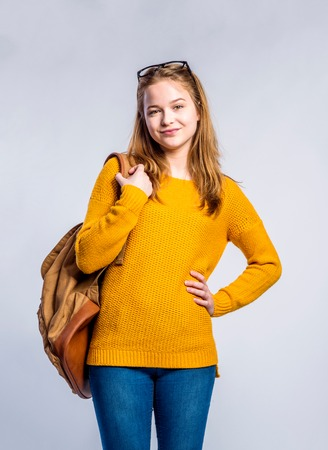tight jeans: Teenage girl in jeans, yellow sweater, holding a backpack, young woman, studio shot on gray background