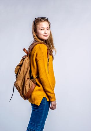 jeans apretados: Adolescente en pantalones vaqueros, suéter amarillo, con mochila en la espalda, mujer joven, estudio disparó sobre fondo gris Foto de archivo