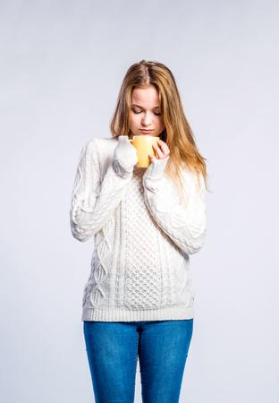 sueter: Adolescente en pantalones vaqueros y suéter blanco, sosteniendo una taza con bebida caliente, mujer joven, estudio disparó sobre fondo gris Foto de archivo