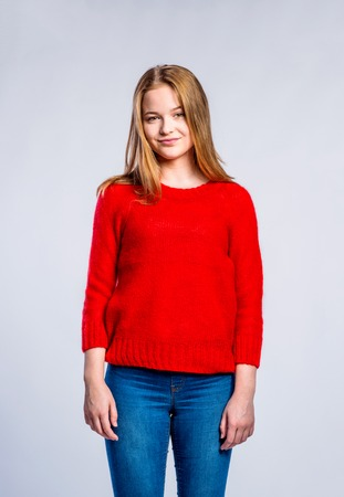 Teenager-Mädchen in Jeans und roten Pullover, junge Frau, Studioaufnahme auf grauem Hintergrund Standard-Bild