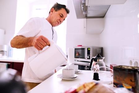 kettles: hombre mayor que prepara el café. Verter el agua caliente del hervidor de agua en las tazas preparadas.