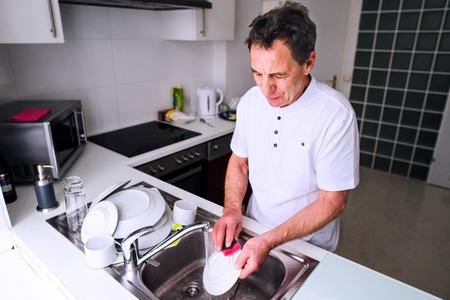 Handen van onherkenbare senior man in wit t-shirt wassen tomaten onder de kraan. Voorbereiding van het ontbijt. Stockfoto