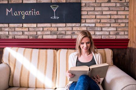 mujeres sentadas: Mujer rubia con el periódico en café sentado en la mesa de café