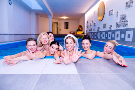 bridesmaids: Cheerful bride and happy bridesmaids in bikinis celebrating hen party in wellness center. Women enjoying a bachelorette party.