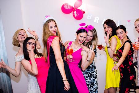 Vrolijke bruid en gelukkige bruidsmeisjes viert vrijgezellenfeest met drankjes. Vrouwen genieten van een vrijgezellenfeest dansen.