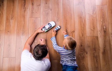 padre e hijo: padre irreconocible con su hijo que juegan con los coches. Estudio tirado en el fondo de madera. Foto de archivo
