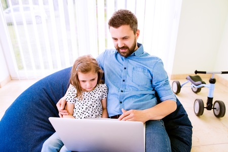bean bag: Father and daughter together, playing on laptop, sitting on bean bag, high angle view Stock Photo