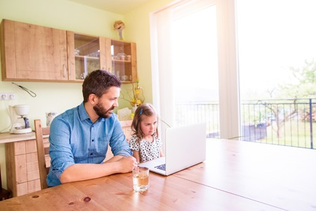 dad and daughter: Father and daughter together, playing on laptop, sitting at the kitchen table