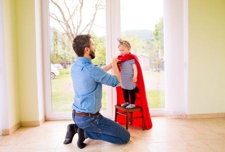 niños vistiendose: padre del inconformista con su linda hija pequeña princesa en rojo capa de superhéroe, vestirla