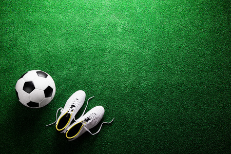 cleats: Soccer ball and cleats against artificial turf, studio shot on green background. Flat lay, copy space. Stock Photo