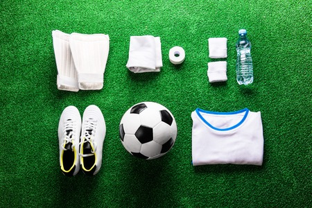 cleats: Soccer ball,cleats and various football stuff against artificial turf. Studio shot on green background. Flat lay, knolling. Stock Photo