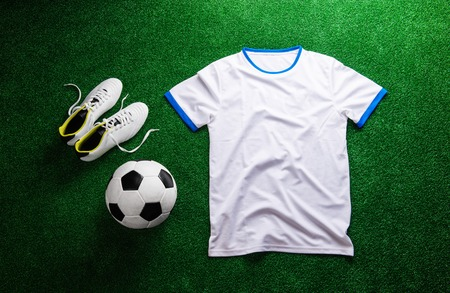 cleats: Soccer ball, cleats, white t-shirt against artificial turf. Studio shot on green background. Flat lay. Stock Photo