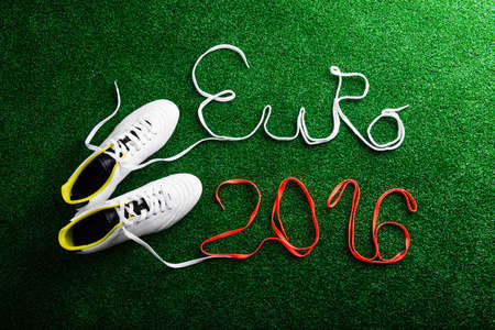 cleats: Cleats and Euro 2016 sign made of shoelaces against artificial turf, studio shot on green background. Flat lay.