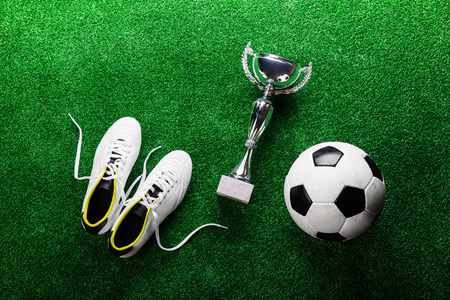 cleats: Soccer ball, cleats and trophy against artificial turf, studio shot on green background. Flat lay.
