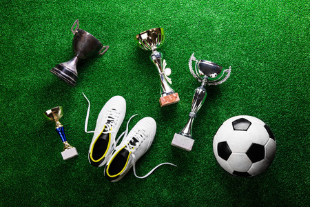winning pitch: Soccer ball, cleats and various trophies and cups against artificial turf, studio shot on green background. Flat lay.