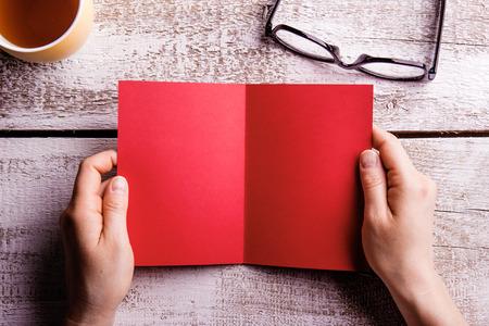 空赤グリーティング カードを保持している認識できない女性の手。一杯の紅茶と眼鏡。木製の背景で撮影スタジオ。フラット レイアウト、スペース