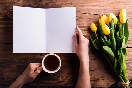 hand lay: Hand of woman holding empty greeting card and coffee. Bouquet of yellow tulips. Studio shot on wooden background. Flat lay, copy space. Stock Photo