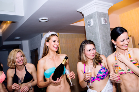 bridesmaids: Cheerful bride and happy bridesmaids in bikinis celebrating hen party with champagne. Women enjoying a bachelorette party.