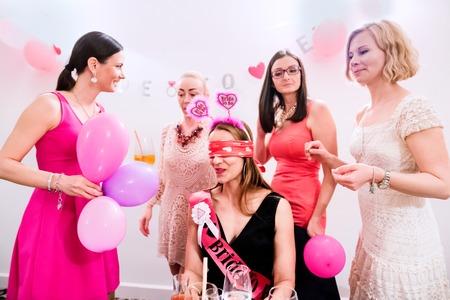 Vrolijke bruid en gelukkige bruidsmeisjes viert vrijgezellenfeest met drankjes. Vrouwen genieten van een vrijgezellenfeest.