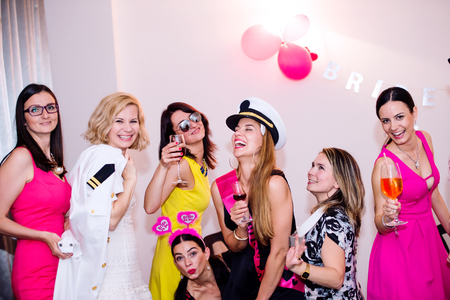 bridesmaids: Cheerful bride and happy bridesmaids celebrating hen party with drinks. Women enjoying a bachelorette party dancing. Stock Photo